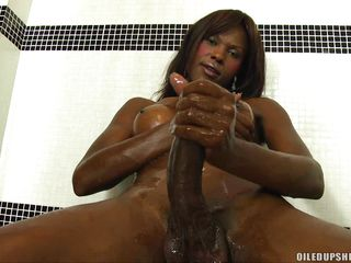 sexy shelady strokes her big black strapon in the shower-room