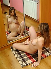 A pregnant teen hottie checks herself out in the mirror